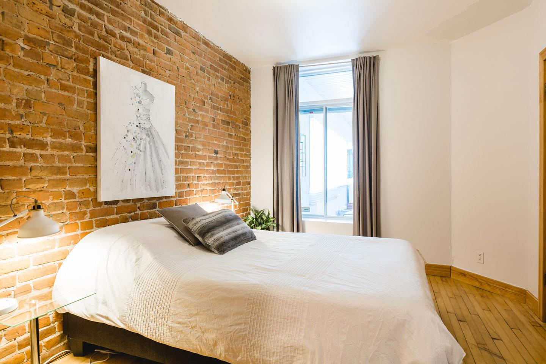 City Chalet : chambre 2 avec mur de brique et lit Queen avec matelas en mousse-mémoire de qualité