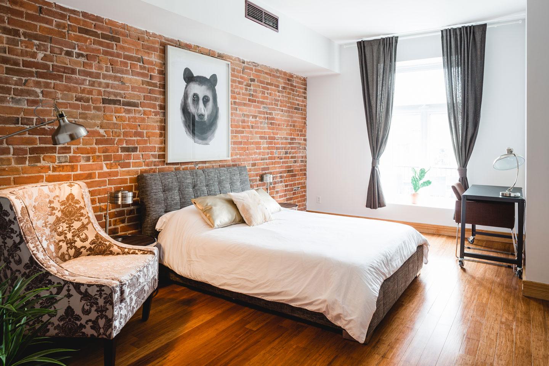 City Chalet : chambre des maîtres très lumineuse avec mur de brique et lit Queen et matelas en mousse-mémoire de qualité