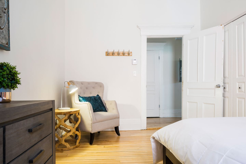 Chic Laurier #2: chambre 2, coin lecture avec fauteuil et lampe d'appoint