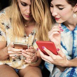 2 femmes consultent leur téléphone mobile